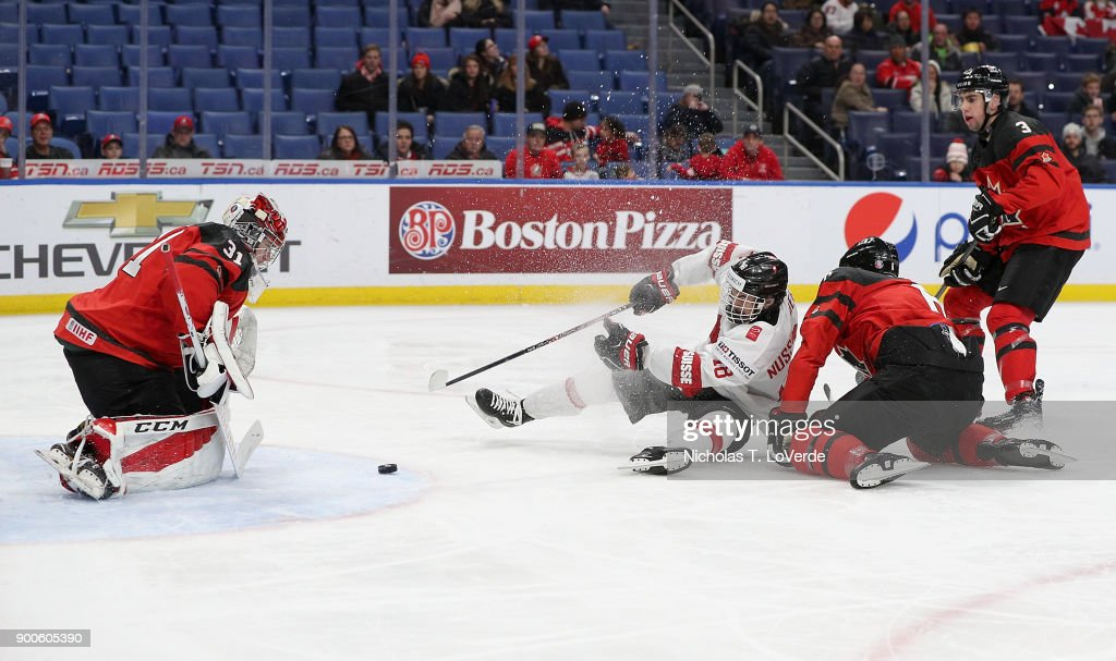 Valentin Nussbaumer #18 of Switzerland draws a tripping penallty before he got his shot off on Carter Hart #31 of Canada during the second period of play in the Quarterfinal IIHF World Junior Championship game at the KeyBank Center on January 2, 2018 in Buffalo, New York.