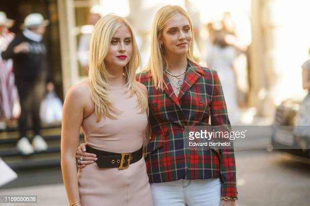 Valentina Ferragni wears a pink sleeveless dress, a Dior large leather belt ; Chiara Ferragni wears a necklace, a checked red and green blazer...