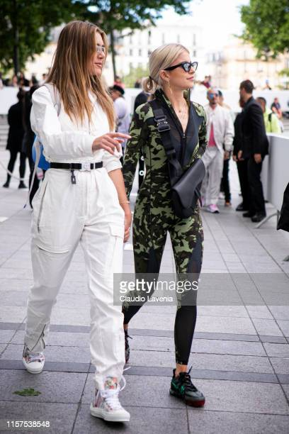 Valentina Ferrero , wearing a cream jumpsuit and colorful sneakers, and Caro Daur , wearing a military print jumpsuit, grey decorated shoes and black...