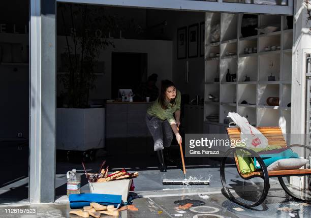 Valentina Stoll carry uses a squeegee to push flood water out of her shop which was flooded along with many businesses at The Barlow market district...