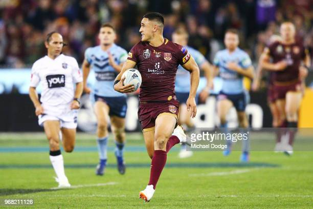 Valentine Holmes of the Maroons runs with the ball to score a try during game one of the State Of Origin series between the Queensland Maroons and...