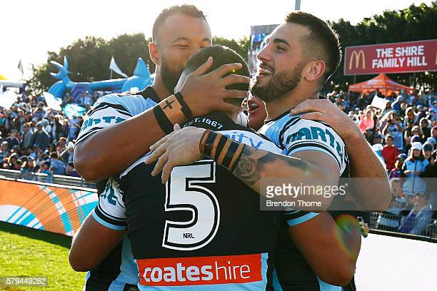 Valentine Holmes of the Sharks celebrates with team mates Jack Bird and Joseph Paulo after scoring a try during the round 20 NRL match between the...