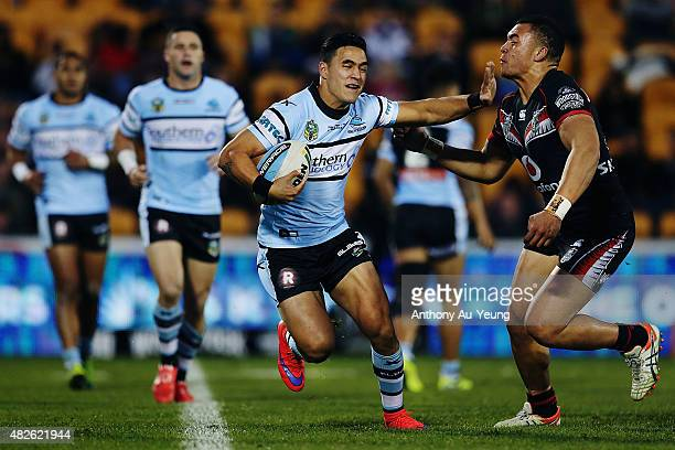 Valentine Holmes of the Sharks fends against Raymond FaitalaMariner of the Warriors during the round 21 NRL match between the New Zealand Warriors...