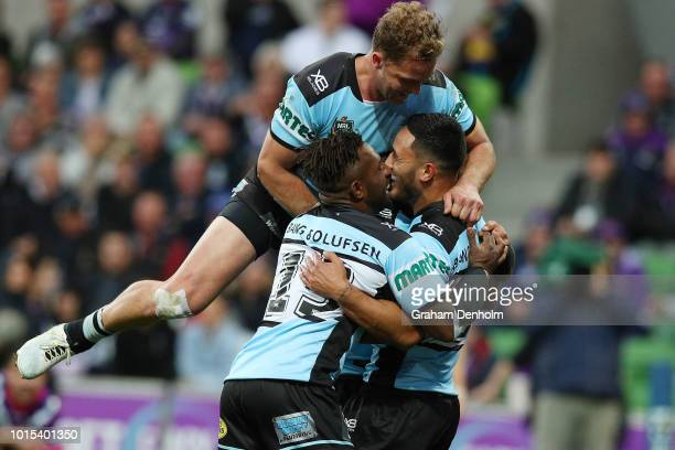 Valentine Holmes of the Sharks is congratulated by his teammates after scoring a try during the round 22 NRL match between the Melbourne Storm and...