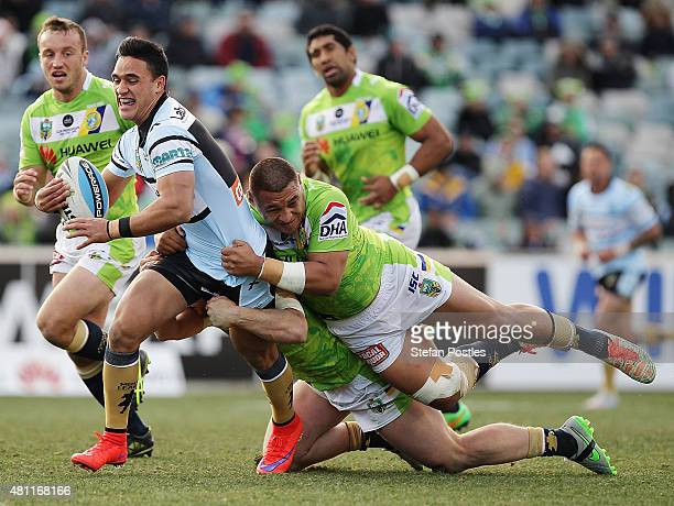 Valentine Holmes of the Sharks is tackled during the round 19 NRL match between the Canberra Raiders and the Cronulla Sharks at GIO Stadium on July...