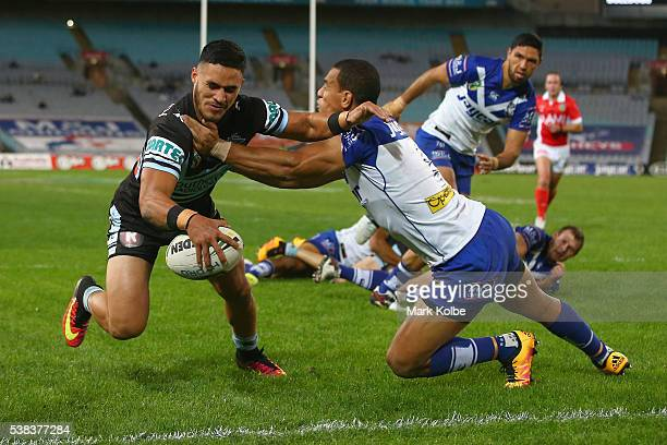 Valentine Holmes of the Sharks scores a try as he is tackled by William Hopoate of the Bulldogs during the round 13 NRL match between the Canterbury...