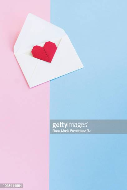 valentine letter in open envelope with an origami  heart shape ready for love message on colored background. copy space - heart month stock photos and pictures