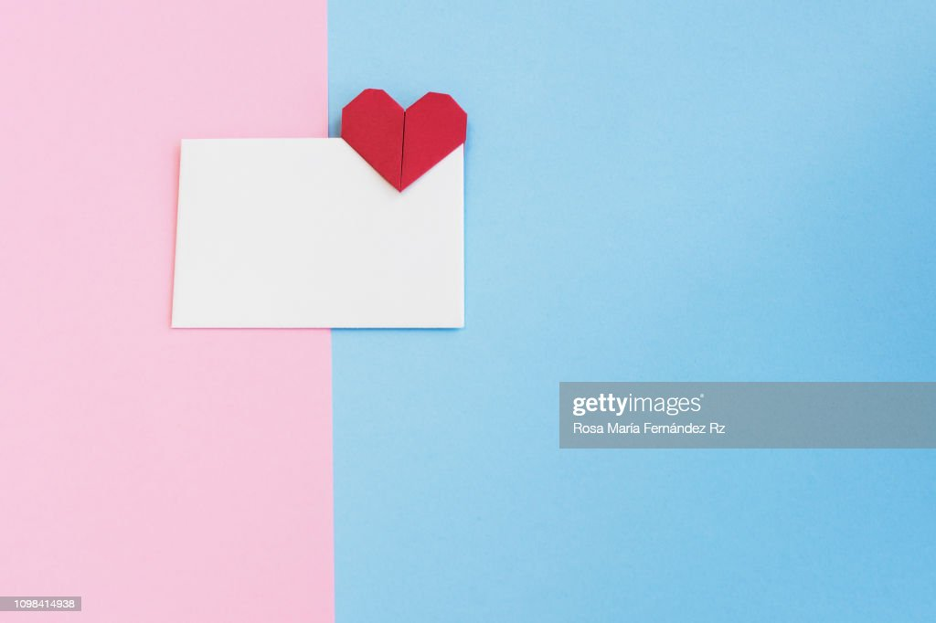 Valentine letter in open envelope with an origami  heart shape ready for love message on colored background. Copy space : Stock Photo