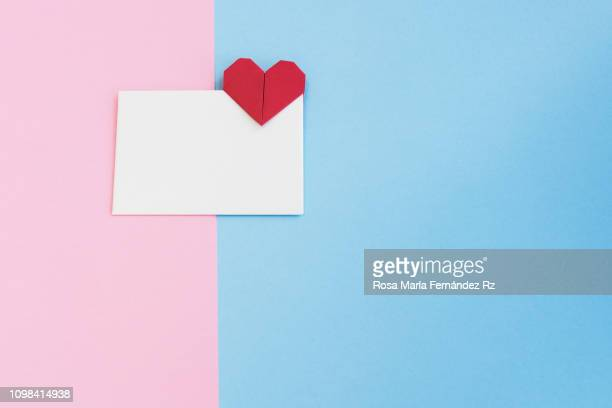 Valentine letter in open envelope with an origami  heart shape ready for love message on colored background. Copy space