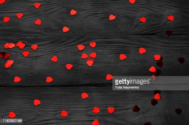 valentine theme love. red confetti hearts on black wooden background. copy space. - february background stock pictures, royalty-free photos & images