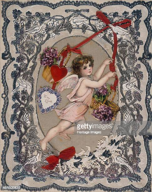 Valentine's card 19th century A decorative border surrounds an image of a cherub carrying two baskets of flowers attached to a red ribbon
