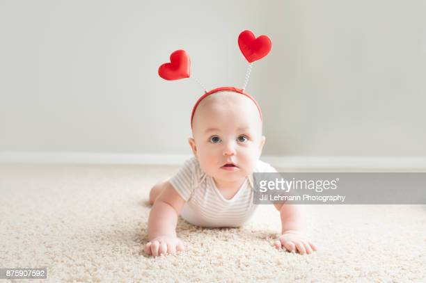 Valentine's Day Baby Poses for Camera Wearing Heart Headband