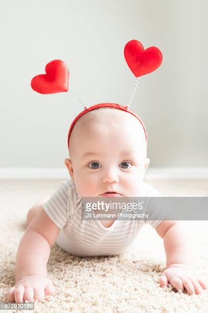 Valentine's Day Baby Poses for Camera Wearing Hearts