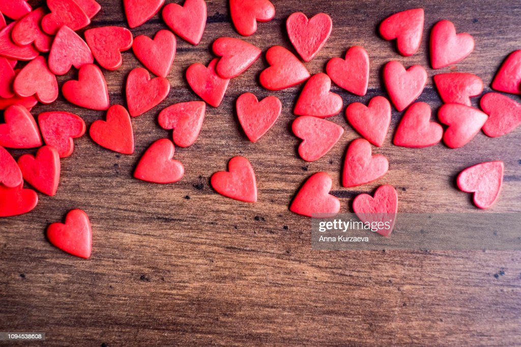 Valentines Day background with red hearts on a wooden table, top view. Red heart shaped candies on a wooden brown background. The concept of Valentines Day. : Stock Photo