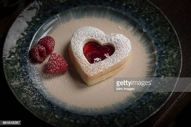 Valentines Day baking, high angle view of a plate with heart shaped biscuits and fresh raspberries.