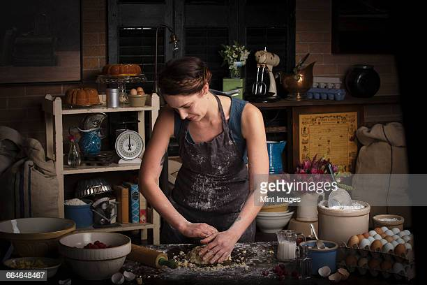 Valentines Day baking, young woman standing in a kitchen, preparing dough for biscuits.