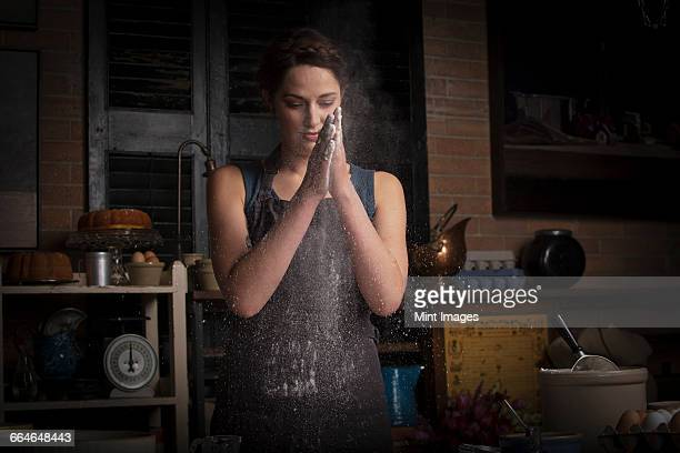 valentines day baking, young woman standing in a kitchen, rubbing flour between her hands. - mehl stock-fotos und bilder