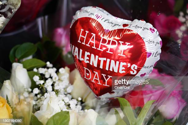 Valentine's Day balloons and flowers are sold outside a convenience store on February 14, 2021 in New York City.