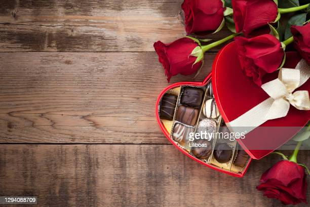 valentine's day box of chocolates and red roses - valentine' day stock pictures, royalty-free photos & images
