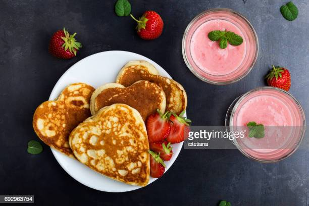 Valentines day breakfast table with heart shaped pancakes and fruit smoothies