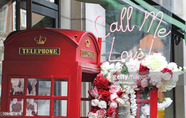 Valentines Day 'Call me Love' display of roses around a telephone box and decorative cycle seen in Mayfair