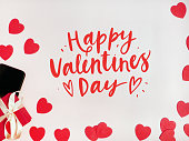 Valentine's day card. Composition with gifts, red hearts, mpbile phone and sign Happy Valentines Day on white surface