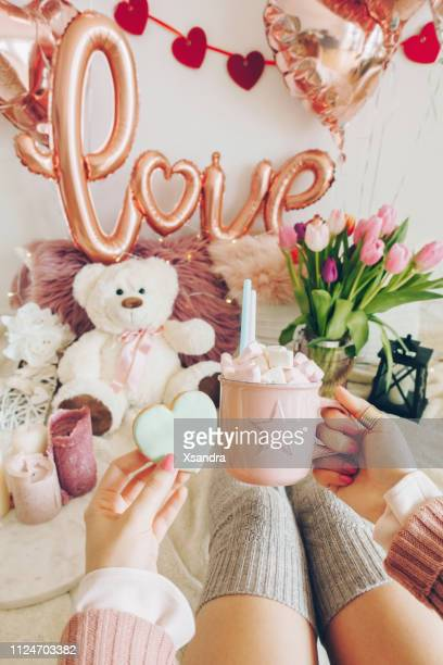 Valentine's day concept: woman's hands holding a cup of cocoa with marshmallows and a heart shaped cookie. Foil balloons decorations in the background.