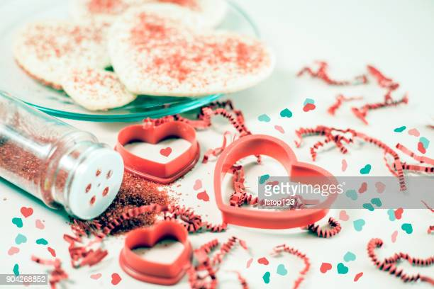 valentine's day cookies and pastry cutters with red sprinkles. - heart month stock photos and pictures