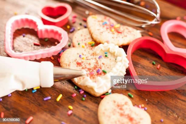 Valentine's Day cookies, baking utensils, ingredients.