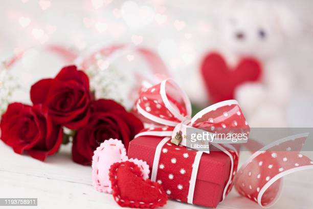 valentine's day gift with red roses against a white background - february stock pictures, royalty-free photos & images