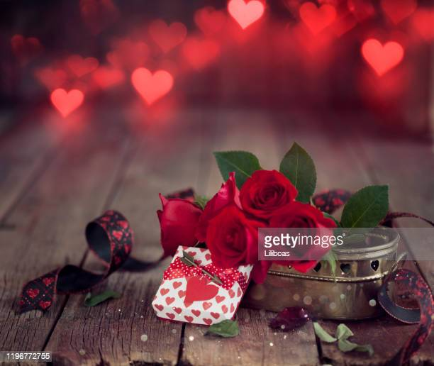 valentine's day gift with red roses on a dark wood background - february background stock pictures, royalty-free photos & images