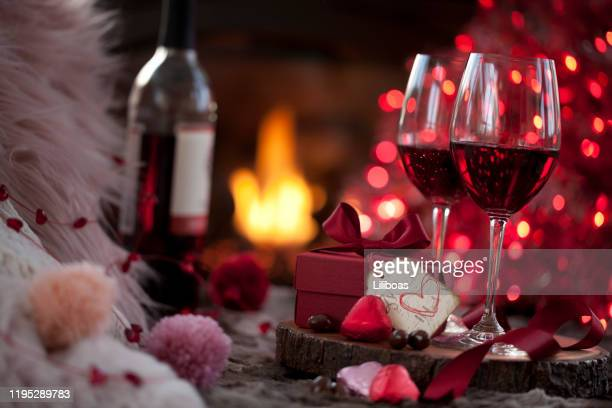 valentine's day red wine and a gift with chocolates in front of the fireplace - valentines day dinner stock pictures, royalty-free photos & images