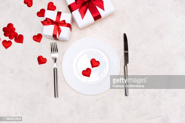 valentine's day table setting with plate, fork, knife, gift box and red heart, on red tablecloth background top view copy space - valentines day dinner stock pictures, royalty-free photos & images