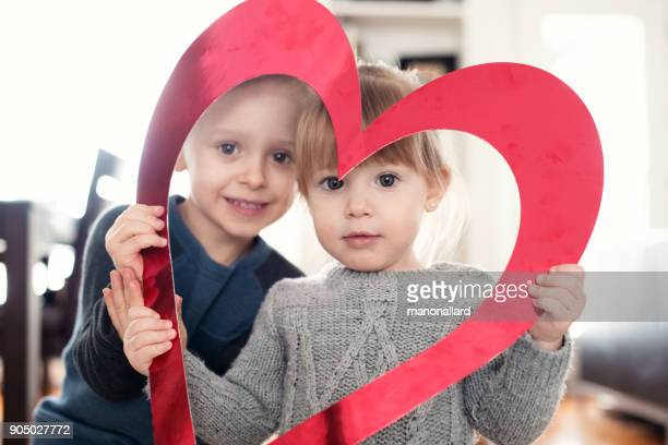 Valentine's Day with a lovely girl and boy holding red heart shape