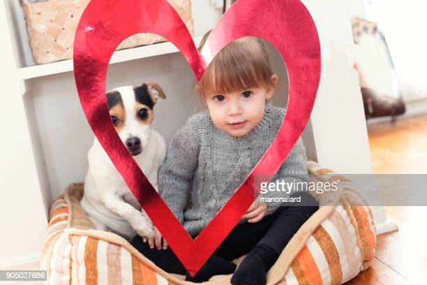 Valentine's Day with a lovely little girl holding red heart shape with her dog