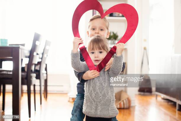 Valentine's Day with two lovely children sister and brother holding heart shape