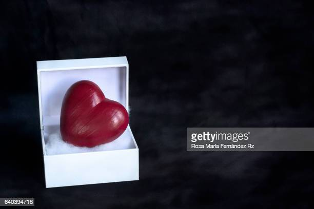 Valentine's heart in a open gift box. Subject captured against soft window lighting over abstract background with copy space.