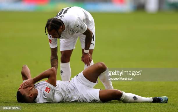Valentino Lazaro of Borussia Moenchengladbach checks on team mate Alassane Plea as he lies injured during the Bundesliga match between Borussia...