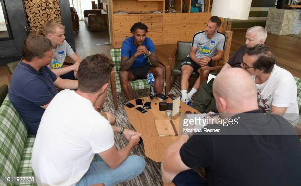 Valentino Lazaro speaks with the journalists next to leader of communication and media Marcus 'Max' Jung of Hertha BSC during the training camp on...