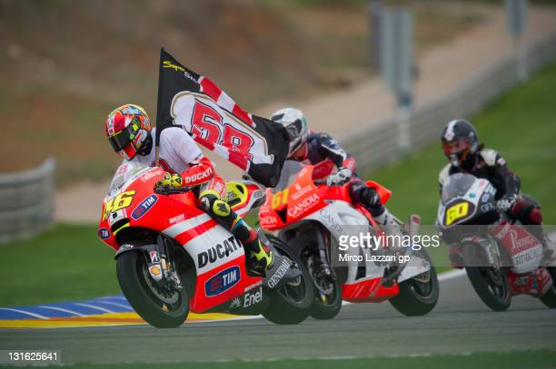 "Valentino Rossi of Italy and Ducati Marlboro Team rides the bike with Marco Simoncelli's flag in front of other riders during the ""Super Sic Tribute..."