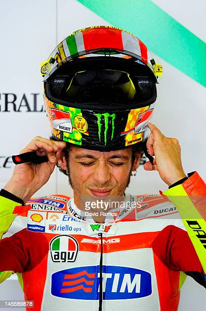Valentino Rossi of Italy and Ducati Team adjusts his helmet at his pit during the qualifying at Circuit de Catalunya on June 2 2012 in Montmelo Spain...