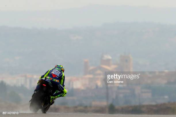 Valentino Rossi of Italy and Movistar Yamaha MotoGP rides backdropped by the Santa Maria la Mayor church in the nearby town of Alcaniz during...