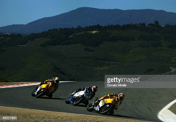 Valentino Rossi of Italy drives his Factory Racing Yamaha in front of Makoto Tamada of Japan on his Konica Minolta Honda and Colin Edwards of the USA...