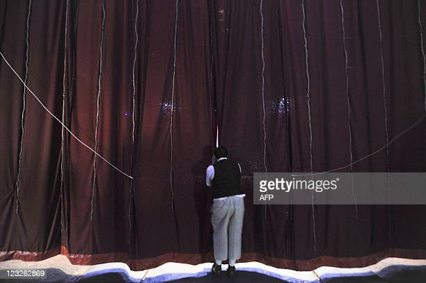 Valentinos Circus' Yilbert 'Chicharito' Alberto peeps through the stage curtain in Caracas on August 31 2011 The start of the Valentinos Circus goes...