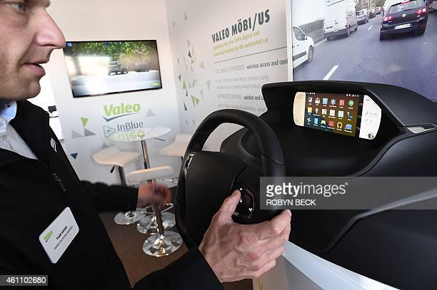 Valeo's Frank Kaiser uses his right thumb on the 18' inch steering wheel touchscreen to access his smartphone as he demonstrates the Mobi/us...