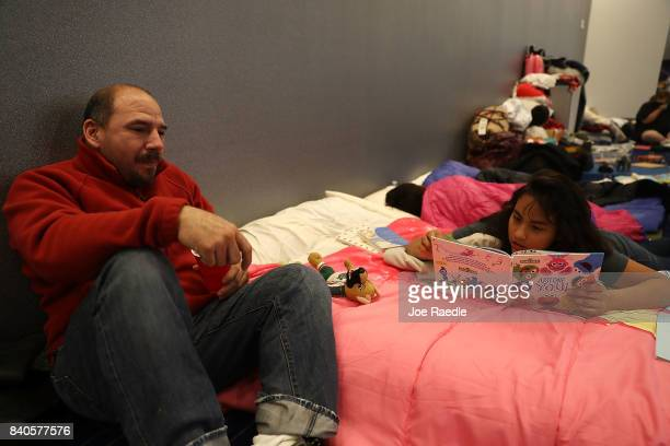 Valeri Delgado reads a book as she and her family take shelter at the George R Brown Convention Center after flood waters from Hurricane Harvey...