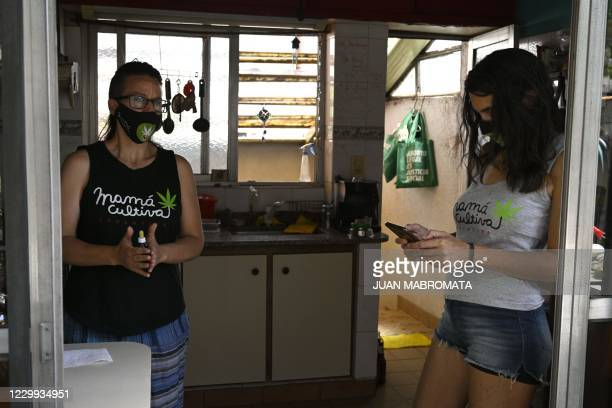 Valeria Salech , member of the self-managing NGO Mama cultiva who has an epileptic son, check her mobile phone while Valeria Rivera prepares...