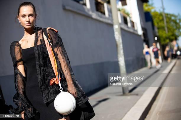 Valeria Semushina wearing a black dress black seethrough jacket and white bag is seen during the Milan Men's Fashion Week Spring/Summer 2020 on June...
