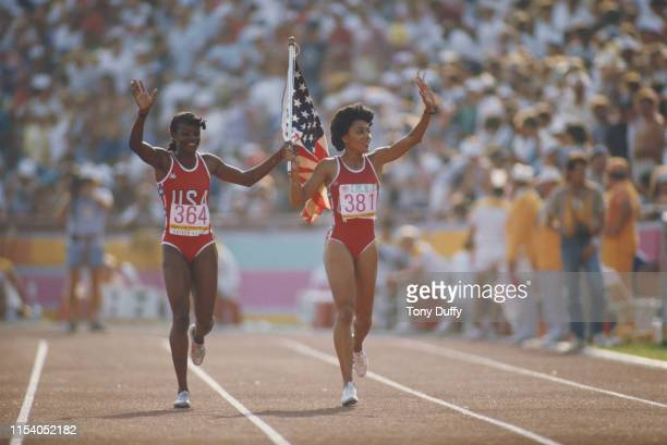 Valerie BriscoHooks and Florence Griffith Joyner of the United States wave the Stars and Stripes flag and celebrate finishing first and second in the...