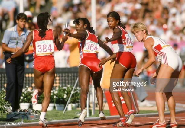 Valerie Brisco-Hooks of the United States takes the baton from teammate Sherri Howard during the Women's 4 x 400 meter relay event of the track and...
